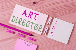 Writing note showing Art Director. Business photo showcasing responsible for overseeing the artistic aspects of a film Colored clothespin papers empty reminder wooden floor background office.