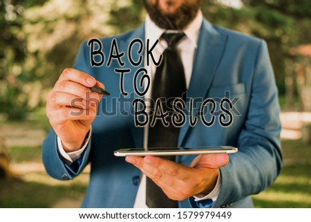 Writing note showing Back To Basics. Business photo showcasing Return simple things Fundamental Essential Primary basis Businessman in blue suite stands with mobile phone in hands.