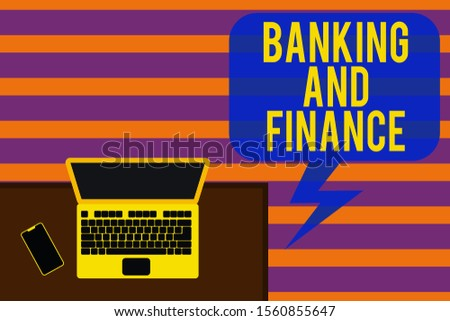 Writing note showing Banking And Finance. Business photo showcasing Accounting and entities stocks Money interests Office working place laptop lying wooden desk smartphone.