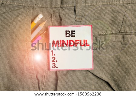 Writing note showing Be Mindful. Business photo showcasing paying close attention to or being conscious of something Writing equipment and blue note paper in pocket of trousers. #1580562238