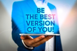 Writing note showing Be The Best Version Of You. Business photo showcasing going to move away from where are start improving Man in the blue suite and white shirt holds mobile phone in the hand.