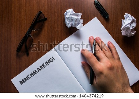 Writing note showing Benchmarking. Business photo showcasing evaluate something by comparison with standard or scores Man hand resting pen open notebook reading glasses lying wooden table. #1404374219