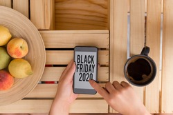 Writing note showing Black Friday 2020. Business photo showcasing day following Thanksgiving Discounts Shopping day woman with laptop smartphone and office supplies technology.