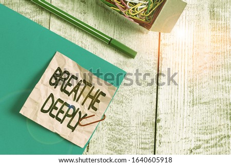 Writing note showing Breathe Deeply. Business photo showcasing to take a large breath of air into your lungs To pause Wrinkle paper and cardboard placed above wooden background.