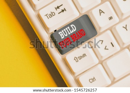 Writing note showing Build Your Brand. Business photo showcasing enhancing brand equity using advertising campaigns White pc keyboard with note paper above the background.