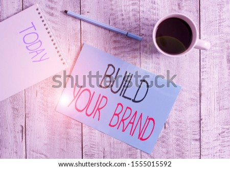 Writing note showing Build Your Brand. Business photo showcasing enhancing brand equity using advertising campaigns Stationary placed next to a cup of black coffee above the wooden table.