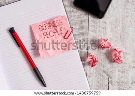 Writing note showing Business People. Business photo showcasing People who work in business especially at an executive level Wrinkle paper notebook and stationary placed on wooden background.