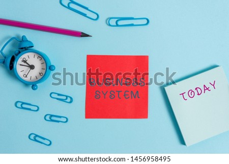 Writing note showing Business System. Business photo showcasing A method of analyzing the information of organizations Alarm clock wakeup clips notepad sticky note pencil colored background. #1456958495