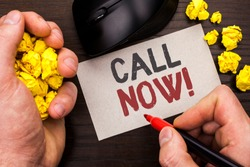 Writing note showing  Call Now. Business photo showcasing Contact Talk Chat Hotline Support Telephony Customer Service written by Man on Note Paper Holding Marker on Wooden background Mouse.
