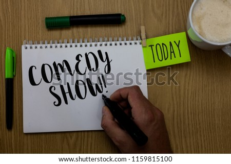 Writing note showing Comedy Show. Business photo showcasing Funny program Humorous Amusing medium of Entertainment Man holding marker notebook clothepin reminder wooden table cup coffee.