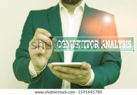 Writing note showing Competitor Analysis. Business photo showcasing assessment of the strengths and weaknesses of rival firm Businessman in the blue suite with lap top pointing with finger.