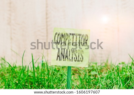 Writing note showing Competitor Analysis. Business photo showcasing assessment of the strengths and weaknesses of rival firm Plain paper attached to stick and placed in the grassy land.