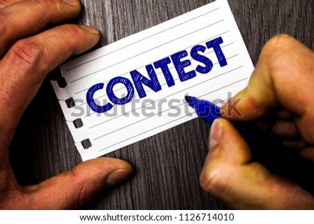 Writing note showing  Contest. Business photo showcasing Game Tournament Competition Event Trial Conquest Battle Struggle Man hold holding marker notebook paper ideas wood wooden background. #1126714010