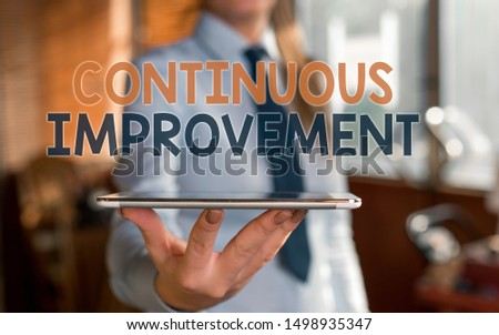 Writing note showing Continuous Improvement. Business photo showcasing ongoing effort to improve products or processes Blurred woman in the background pointing with finger in empty space.