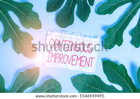 Writing note showing Continuous Improvement. Business photo showcasing ongoing effort to improve products or processes Leaves surrounding notepaper above empty soft pastel table.
