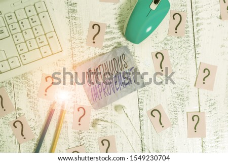 Writing note showing Continuous Improvement. Business photo showcasing ongoing effort to improve products or processes Writing tools and scribbled paper on top of the wooden table.