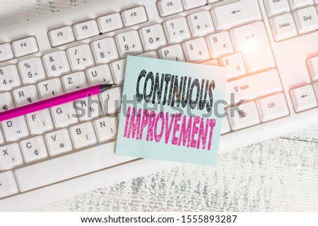 Writing note showing Continuous Improvement. Business photo showcasing ongoing effort to improve products or processes Keyboard office supplies rectangle shape paper reminder wood.