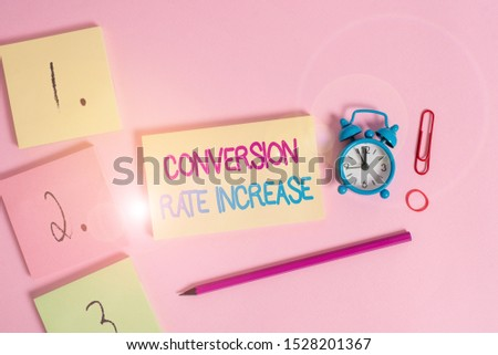Writing note showing Conversion Rate Increase. Business photo showcasing Ratio of Total Visitors who perform desired actions Blank notepads marker rubber band alarm clock clip colored background.