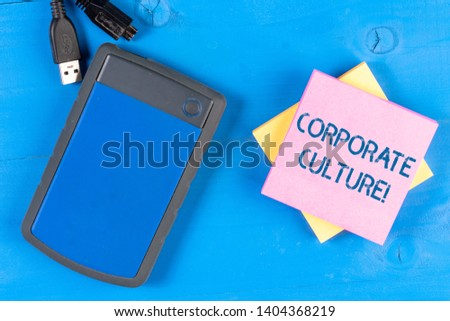Writing note showing Corporate Culture. Business photo showcasing beliefs and attitudes that characterize a company Electronic device USB memory colored sticky note pad wooden background. #1404368219
