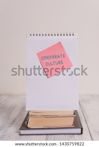 Writing note showing Corporate Culture. Business photo showcasing pervasive values and attitudes that characterize a company Stacked books spiral note book sticky lying vintage retro wooden table. #1430759822