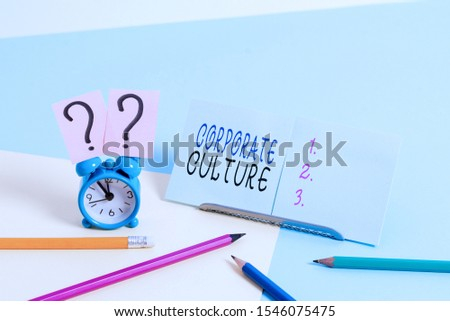 Writing note showing Corporate Culture. Business photo showcasing pervasive values and attitudes that characterize a company Mini size alarm clock beside stationary on pastel backdrop.