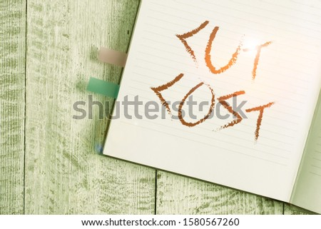 Writing note showing Cut Cost. Business photo showcasing Measures implemented to reduced expenses and improved profit Notebook stationary placed above classic wooden backdrop.