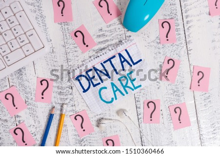 Writing note showing Dental Care. Business photo showcasing maintenance of healthy teeth or to keep it clean for future Writing tools and scribbled paper on top of the wooden table.