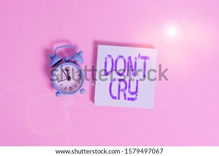 Writing note showing Don T Cry. Business photo showcasing Shed tears typically as an expression of distress pain or sorrow Vintage alarm clock wakeup blank notepad sticky note colored background. #1579497067