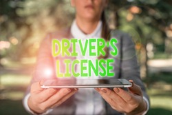 Writing note showing Driver S License. Business photo showcasing a document permitting a demonstrating to drive a motor vehicle Outdoor scene with business woman holds lap top with touch screen.