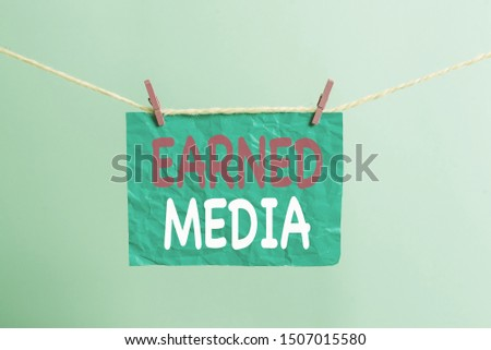 Writing note showing Earned Media. Business photo showcasing Publicity gained through promotional efforts by multimedia Clothesline clothespin rectangle shaped paper reminder white wood desk.