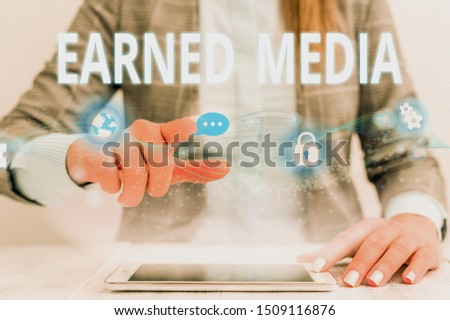 Writing note showing Earned Media. Business photo showcasing Publicity gained through promotional efforts by multimedia Female human wear formal work suit presenting smart device.