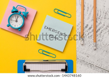 Writing note showing Emergency Plan. Business photo showcasing Procedures for response to major emergencies Be prepared Notepads paper sheet clipboard markers alarm clock wooden background. #1443748160