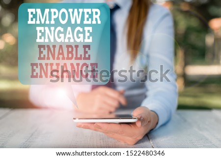 Writing note showing Empower Engage Enable Enhance. Business photo showcasing Empowerment Leadership Motivation Engagement Female business person sitting by table and holding mobile phone.