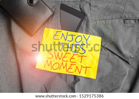 Writing note showing Enjoy This Sweet Moment. Business photo showcasing encouraging someone to love his life timeline Smartphone device inside trousers front pocket with wallet.
