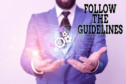 Writing note showing Follow The Guidelines. Business photo showcasing Manual of Style Follow a Specified Rule Accordingly Male human wear formal suit presenting using smart device.