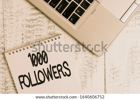 Writing note showing 1000 Followers. Business photo showcasing number of individuals who follows someone in Instagram Top trendy metallic laptop blank spiral notepad lying on wooden table.