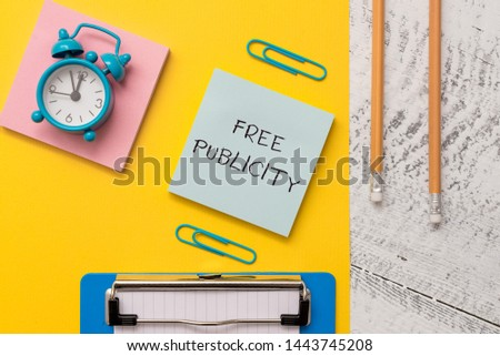 Writing note showing Free Publicity. Business photo showcasing Promotional marketing Mass media Public Relations Editorial Notepads paper sheet clipboard markers alarm clock wooden background.
