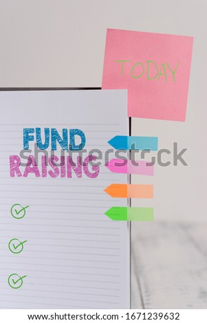 Writing note showing Fund Raising. Business photo showcasing the act of seeking to generate financial support for a charity Hard cover note book sticky note arrow banner inserted clear background. Photo stock ©
