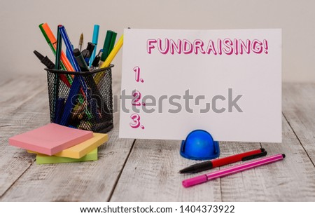 Writing note showing Fundraising. Business photo showcasing seeking to generate financial support for charity or cause Stationary and computer mouse with globe on the wooden desk. #1404373922