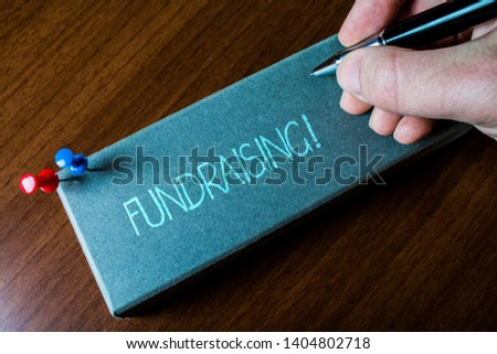 Writing note showing Fundraising. Business photo showcasing seeking to generate financial support for charity or cause Close up left man right hand holding pen fixed pins lying wooden table. #1404802718