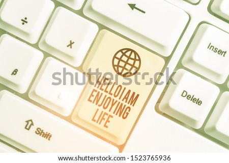 Writing note showing Hello I Am Enjoying Life. Business photo showcasing Happy relaxed lifestyle Enjoy simple things White pc keyboard with note paper above the white background. #1523765936