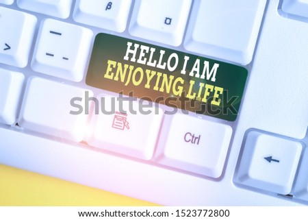 Writing note showing Hello I Am Enjoying Life. Business photo showcasing Happy relaxed lifestyle Enjoy simple things White pc keyboard with note paper above the white background. #1523772800