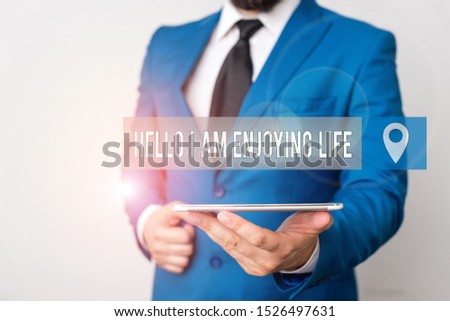 Writing note showing Hello I Am Enjoying Life. Business photo showcasing Happy relaxed lifestyle Enjoy simple things Businessman in blue suite with a tie holds lap top in hands.