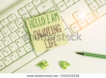 Writing note showing Hello I Am Enjoying Life. Business photo showcasing Happy relaxed lifestyle Enjoy simple things Green note paper with pencil on white background and pc keyboard.