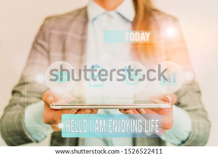 Writing note showing Hello I Am Enjoying Life. Business photo showcasing Happy relaxed lifestyle Enjoy simple things Female human wear formal work suit presenting smart device. #1526522411