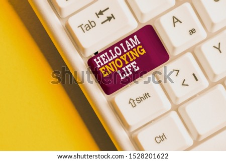 Writing note showing Hello I Am Enjoying Life. Business photo showcasing Happy relaxed lifestyle Enjoy simple things White pc keyboard with note paper above the white background. #1528201622