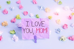 Writing note showing I Love You, Mom. Business photo showcasing Loving message emotional feelings affection warm declaration Colored crumpled papers empty reminder blue floor background clothespin.