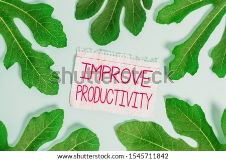 Writing note showing Improve Productivity. Business photo showcasing to increase the machine and process efficiency Leaves surrounding notepaper above empty soft pastel table.