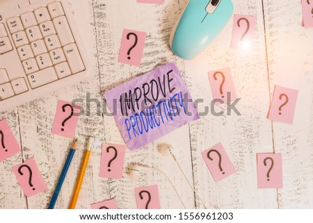 Writing note showing Improve Productivity. Business photo showcasing to increase the machine and process efficiency Writing tools and scribbled paper on top of the wooden table.