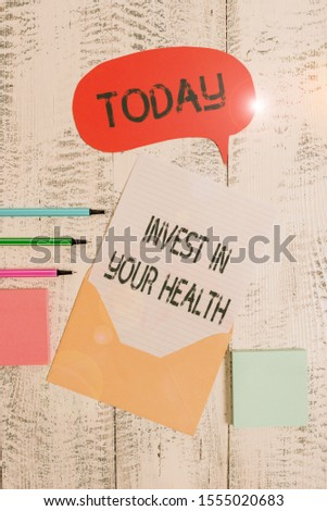 Writing note showing Invest In Your Health. Business photo showcasing Live a Healthy Lifestyle Quality Food for Wellness Envelop speech bubble paper sheet ballpoints notepads wooden background.